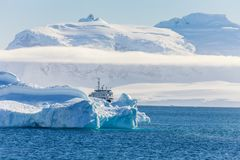 Blue antarctic cruise vessel among the icebergs with glacier in. Background, Neco bay, Antarctica Royalty Free Stock Images
