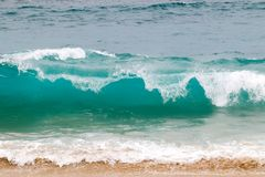 Blue and aquamarine color sea waves and yellow sand  with white foam. Marine beach background. Blue and aquamarine color sea waves and yellow sand  with white royalty free stock photography