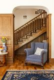 Blue armchair against wooden stairs in classic living room inter. Ior with flowers and carpet. Real photo stock photo