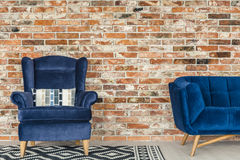 Blue armchair and pattern rug Stock Image