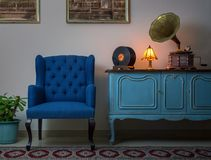Blue armchair, vintage wooden light blue sideboard, lighted antique table lamp, old phonograph gramophone and vinyl records. Interior shot of blue armchair royalty free stock photos