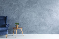 Blue armchair and wood side table Royalty Free Stock Photos