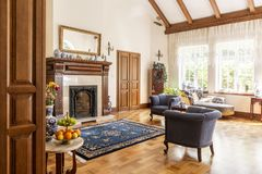 Blue armchairs and patterned carpet in front of wooden fireplace in sophisticated interior. Real photo stock image
