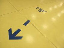 Blue arrow. On yellow floor Stock Photos