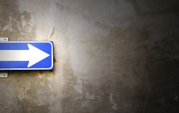 Blue Arrow. Photo detail of an arrow sign stuck on old wall crumbling Royalty Free Stock Photography