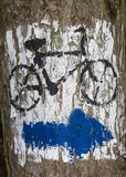 Blue arrow painted on tree bark. Blue arrow sign in white background and bicycle sign  painted on tree bark Stock Images