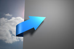 Blue arrow pointing against sky around wall Royalty Free Stock Images