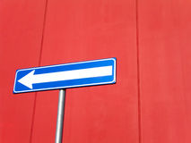 Blue arrow sign on red. A blue directional arrow or sign on a bright red background stock photos