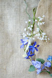 Blue artificial flowers on sackcloth Stock Photos