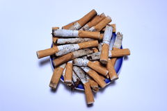 Blue ashtray filled with used cigarette butts on white and blue background Stock Image