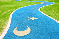 Blue asphalt path via green grass Stock Photo
