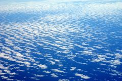 Blue atmosphere. Large and deep blue sky with beautiful clouds spreading over blue ocean as seen from a plane. Cotton white clouds in natural gradient of blue Royalty Free Stock Photo