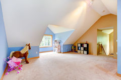 Blue attic living room with toys and play area. Royalty Free Stock Photo
