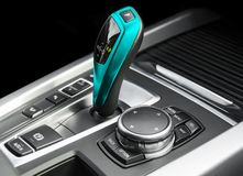 Blue Automatic gear stick of a modern car. Modern car interior details. Close up view. Car detailing. Automatic transmission lever. Shift isolated on black stock illustration