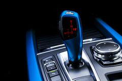 Blue Automatic gear stick of a modern car. Modern car interior details. Close up view. Car detailing. Automatic transmission lever stock image