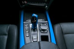 Blue Automatic gear stick transmission of a modern car, multimedia and navigation control buttons. Car interior details. Royalty Free Stock Photo