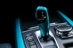 Blue Automatic gear stick transmission of a modern car, multimedia and navigation control buttons. Car interior details. Transmission shift stock photography