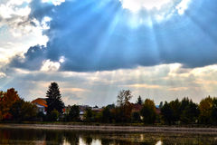 Blue autumn sky with clouds in landscape. Autumn sun and clouds, pond, houses in village Stock Photo