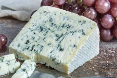 Blue Auvergne semi-hard AOP French blue cheese made from raw cow milk in Auvergne, France served as dessert with grapes. Piece of Blue Auvergne semi-hard AOP stock photo