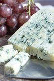 Blue Auvergne semi-hard AOP French blue cheese made from raw cow milk in Auvergne, France served as dessert with grapes. Piece of Blue Auvergne semi-hard AOP stock photos