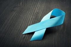 Blue awareness ribbon on a black desk. Prostate Cancer. Concept stock images