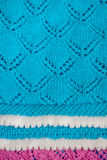 Blue baby blanket with a white border, hand-knitted. Background Stock Photos