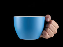 Blue - baby blue color cup - mug on black background. Woman hand holding an gentle blue - baby blue color cup - mug on black background Stock Images