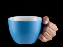 Blue - baby blue color cup - mug on black background. Woman hand holding an gentle blue - baby blue color cup - mug on black background Royalty Free Stock Photography
