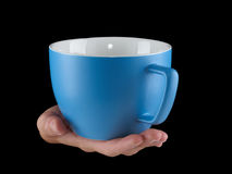 Blue - baby blue color cup - mug on black background. Woman hand holding an gentle blue - baby blue color cup - mug on black background Stock Photos