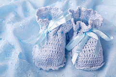 Blue baby booties. On blue background royalty free stock photo