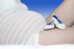 Blue baby booties rest against full-term tummy stock image
