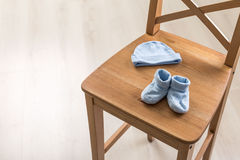 Blue baby clothes on chair royalty free stock photography