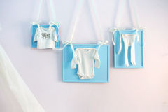 Blue baby clothes on the clothesline ribbons on the wall Stock Photos