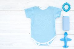 Blue baby clothes for little boy. Bodysuit, toys, cosmetics on white wooden background top view copy space. Blue baby clothes for little boy. Bodysuit, toys royalty free stock photo