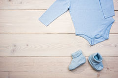 Blue baby clothes. On wooden dekstop. Mock up stock image