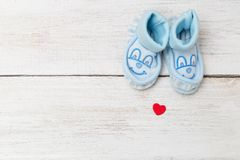 Blue baby`s bootees on wooden background. Mockup Stock Images