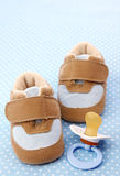 Blue baby shoes and dummy Stock Images