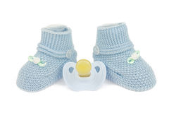 Blue baby shoes and dummy Stock Photos