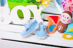 Blue baby shoes and flowers Stock Images