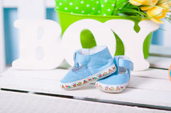 Blue baby shoes and flowers Royalty Free Stock Photos