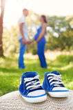 Blue baby shoes on grass. Parents. A pregnant woman. Royalty Free Stock Image