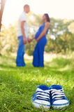Blue baby shoes on grass. Parents. A pregnant woman. Stock Image