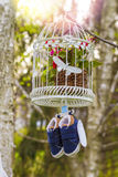 Blue baby shoes hanging from a cage Stock Image