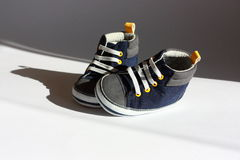 Blue baby shoes. Blue sneakers baby shoes in sunlight Royalty Free Stock Photography