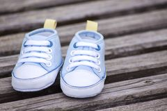 Blue baby shoes on a wooden surface Stock Photography