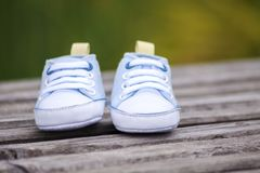 Blue baby shoes on a wooden surface Stock Photo