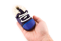Blue baby sneaker shoe in hand Stock Photography