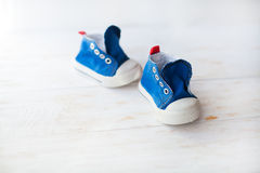 Blue baby sneakers on a wood floor Royalty Free Stock Photos