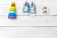 Blue baby sneakers and wooden toys. View from above Stock Images