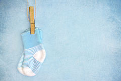 Blue baby socks on a textured background. Blue baby socks on a textured rustic background with copy space stock photo